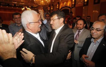 Member of the Syrian opposition Hisham Marwah (R) congratulates new chief of Syrian National Council (SNC) George Sabra after the results of the executive committee election during General Assembly of the SNC meeting in Doha, November 9, 2012. REUTERS/Mohammed Dabbous