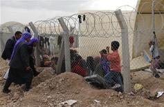 Al menos 20 hombre de seguridad sirios murieron cuando dos vehículos cargados de explosivos entraron en un campamento militar el sábado en la ciudad de Derá, en el sur de Siria, dijo un órgano de supervisión de la oposición, en lo que parece ser un doble ataque suicida llevado a cabo por fuerzas rebeldes. En la imagen, hombres hablan refugiados sirios recién llegados a un campamento de refugiados cerca de la ciudad de Ceylanpinar, en la provincia turca de Sanliurfa, el 10 de noviembre de 2012. Miles de sirios huyeron de su país el viernes en uno de los mayores éxodos de refugiados en la guerra civil que dura ya casi 20 meses después de que los rebeldes capturasen una ciudad fronteriza. La ONU advirtió que millones más que aún permanecen en Siria necesitan ayuda con la llegada del invierno. REUTERS/Murad Sezer