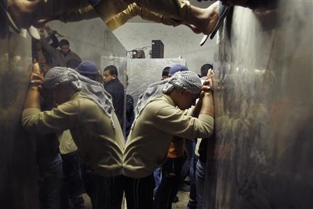 A Palestinian man is reflected in a hospital morgue as he reacts upon the death of his relative in Israeli shelling in Gaza City November 10, 2012. REUTERS/Ahmed Zakot