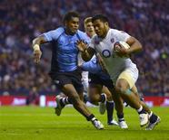<p>L'Anglais Mako Vunipola tente d'inscrire un essai sous la pression des Fidjiens. L'Angleterre a réussi samedi un départ en trombe lors du premier des quatre test-matches qu'elle disputera à Twickenham et a inscrit un record de sept essais contre les Iles Fidji finalement battues 54-12. /Photo prise le 10 novembre 2012/REUTERS/Russell Cheyne</p>