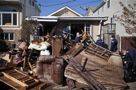 Members of the United States Coast Guard help clear a house in the Midland Beach neighborhood, where many homes are set to be demolished due to Hurricane Sandy, in Staten Island, New York November 9, 2012. REUTERS/Andrew Burton