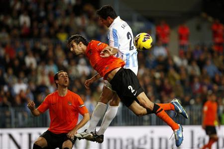 Malaga's Roque Santa Cruz (R) fights for the ball with Real Sociedad's Carlos Martinez (C) during their Spanish First Division soccer match at La Rosaleda stadium in Malaga, southern Spain November 10, 2012. REUTERS/Jon Nazca