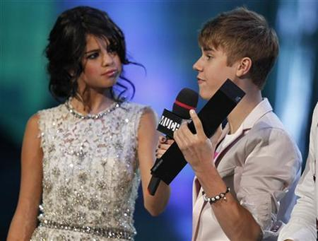 Justin Bieber accepts the award for ''Ur Fav Artist'' for his song ''Somebody to Love'' from host Selena Gomez during the MuchMusic Video Awards in Toronto, June 19, 2011. REUTERS/Fred Thornhill/Files