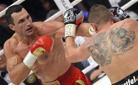 Ukrainian WBA, WBO, IBO and IBF heavy weight boxing world champion Vladimir Klitschko (L) lands a punch during his title fight against Polish challenger Mariusz Wach in Hamburg November 10, 2012. REUTERS/Fabian Bimmer