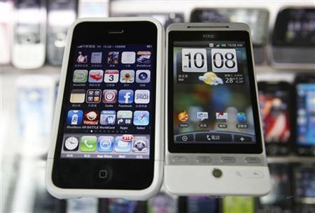 A HTC smartphone (R) and an Apple iPhone are displayed for the photographer at a mobile phone shop in Taipei March 3, 2010. Apple Inc sued Taiwan's HTC Corp, which makes touchscreen smartphones using Google software, accusing it of infringing 20 hardware and software patents related to the iPhone. REUTERS/Nicky Loh (TAIWAN - Tags: BUSINESS)