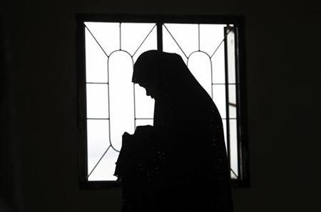 A Muslim woman is silhouetted as their community offers prayers of peace for recent violent protests and attacks in the Islamic world against the U.S., at a mosque in Marikina City, Metro Manila September 14, 2012. REUTERS/Cheryl Ravelo/Files