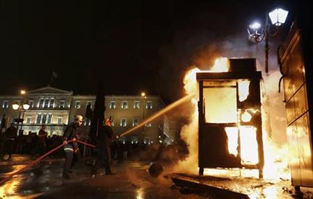 Firefighters try to extinguish a bus station booth which was set on fire by angry protesters in front of the parliament in Syntagma square in central Athens November 7, 2012. REUTERS/Yannis Behrakis