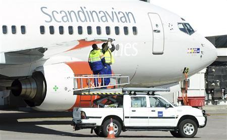 Technicians work on the wing of a Scandinavian airline SAS Boeing 737 aircraft at the Stockholm-Arlanda airport in Sweden May 3, 2012. REUTERS/Johan Nilsson/Scanpix