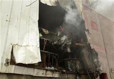 Israel dijo que estaba preparado para intensificar los ataques contra la Franja de Gaza el domingo tras una oleada de cohetes y morteros lanzados por Hamás y otras facciones en el enclave palestino. En la imagen, un palestino intenta sofocar un fuego tras el impacto de un proyectil de un tanque israelí en una fábrica en la Franja de Gaza, el 11 de noviembre de 2012. REUTERS/Ibraheem Abu Mustafa