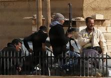 Los grupos de la oposición siria han firmado un acuerdo inicial para formar una nueva coalición de las fuerzas que luchan para derrocar al régimen del presidente Bashar el Asad, dijeron el domingo delegados sirios en las negociaciones en Doha. En la imagen, un combatiente del Ejército Libre Sirio sostiene una ametralladora durante un descanso en la ciudad siria de Ras al-Ain, cerca de la frontera turca, el 11 de noviembre de 2012. REUTERS/Murad Sezer