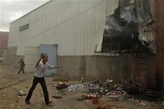A Palestinian walks near a factory after it was hit by an Israeli tank shell in the northern Gaza Strip November 11, 2012. Israel said it was poised to escalate attacks on the Gaza Strip on Sunday following a surge of rocket and mortar salvoes by Hamas and other Palestinian factions. REUTERS/Ibraheem Abu Mustafa (GAZA - Tags: POLITICS CIVIL UNREST)