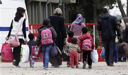 A Syrian family from the northern town of Ras al-Ain, returning their home, walk through a border crossing in Ceylanpinar on the Turkish-Syrian border, Sanliurfa province, November 11, 2012. REUTERS/Murad Sezer