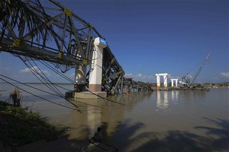 A man sits under the Radana Thinga Bridge over the Irrawaddy River, still under construction, after it collapsed following an earthquake near Singgu Township November 11, 2012. An earthquake struck central Myanmar on Sunday near its second-biggest city, Mandalay, killing at least six people, with the death toll likely to rise as part of an unfinished bridge fell into the Irrawaddy River and several workers were missing. REUTERS-Stringer