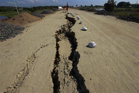 A damaged road is marked with flags after an earthquake struck an area near Kyauk Myaung November 11, 2012. An earthquake struck central Myanmar on Sunday near its second-biggest city, Mandalay, killing at least six people, with the death toll likely to rise as part of an unfinished bridge fell into the Irrawaddy River and several workers were missing. REUTERS/Stringer