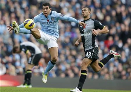 Manchester City's Carlos Tevez (L) jumps for the ball ahead of Tottenham Hotspur's Steven Caulker during their English Premier League soccer match at The Etihad Stadium in Manchester, northern England, November 11, 2012. REUTERS/Phil Noble