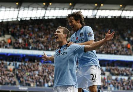 Manchester City's Edin Dzeko (L) celebrates with teammate David Silva after scoring his side's second goal during their English Premier League soccer match against Tottenham Hotspur at The Etihad Stadium in Manchester, northern England, November 11, 2012. REUTERS/Phil Noble
