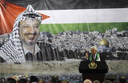 Palestinian President Mahmoud Abbas stands in front of a banner with a picture of late Palestinian leader Yasser Arafat during a ceremony marking the eighth anniversary of his death in the West Bank city of Ramallah November 11, 2012. REUTERS/Mohamad Torokman