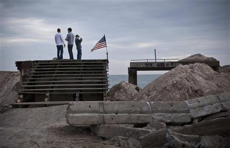 Three volunteers stand on the remains of the infrastructure of the Rockaway Beach boardwalk, which was destroyed by Hurricane Sandy on October 29, in the Rockaway Beach neighborhood of Queens, New York, November 10, 2012. REUTERS/Andrew Burton