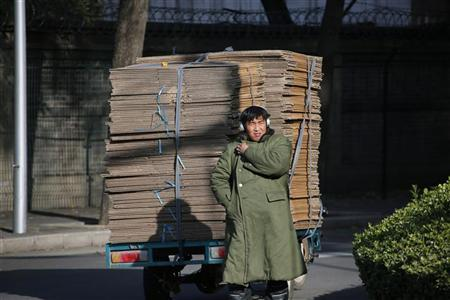 A delivery man listens to the radio as he stands beside his three-wheeled vehicle carrying cardboard in Beijing November 11, 2012. REUTERS/Petar Kujundzic