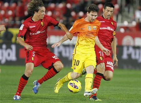 Barcelona's Lionel Messi (C) is challenged by Mallorca's Tomas Pina (L) and Marti during their Spanish first division soccer match at Iberostar stadium in Mallorca November 11, 2012. REUTERS/Enrique Calvo