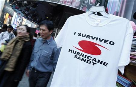 People walk past a ''I Survived Hurricane Sandy'' t-shirt hanging on a rack for sale in Times Square in New York November 11, 2012. REUTERS/Carlo Allegri