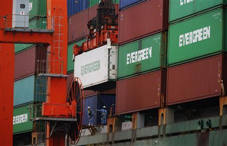 Workers unload a container from a cargo ship at a port in Tokyo November 12, 2012. Japan's economy shrank 0.9 percent in the three months to September, marking the first contraction in three quarters, adding to signs that slowing global growth and tensions with China are nudging the world's third-largest economy into recession. REUTERS/Yuriko Nakao