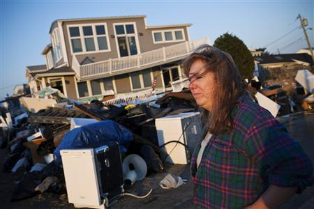 Evelyn Faherty surveys the damage to her home after Hurricane Sandy swept through the Breezy Point neighborhood of Queens, New York, November 11, 2012. REUTERS/Andrew Burton