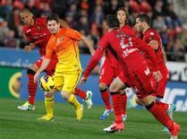 Lionel Messi marcó dos goles el domingo, remontando el partido de Liga del Barça ante el Real Mallorca que terminó 4-2 y marcó la décima victoria azulgrana en 11 partidos. En la magen, el jugador del Barcelona, Lionel Messi, controla el balón rodeado por jugadores del Mallorca durante su partido de Liga en el estadio Iberostar en Mallorca, el 11 de noviembre de 2012. REUTERS/Enrique Calvo