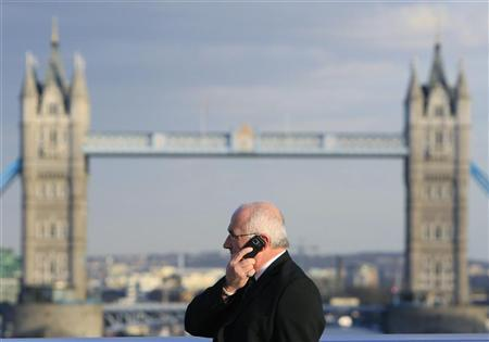 A man talks on a mobile telephone in front of Tower Bridge whilst walking across London Bridge in London March 1, 2010. REUTERS/Luke MacGregor