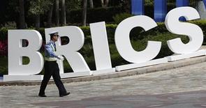 Полицейский проходит мимо знака стран БРИК в Сане, 13 апреля 2011 года. Ведущие страны развивающегося рынка обсуждают возможность накопления валютных резервов на сумму до $240 миллиардов, чтобы защититься от краткосрочного давления на ликвидность, согласно документам, где описываются планы пяти стран БРИК. REUTERS/Jason Lee