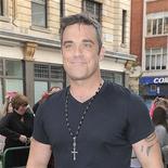 Robbie Williams era el rey de la lista británica de éxitos pop el domingo después de asegurarse el número uno tanto con uno de sus sencillos como con su disco, dijo la Compañía Oficial de Listas de Éxitos. En la imagen, de 10 de septiembre, Robbie Williams llegando a los estudios de Radio 1 en Londres.