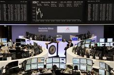 Traders are pictured at their desks in front of the DAX board at the Frankfurt stock exchange November 12, 2012. REUTERS/Remote/Tobias Schwarz (GERMANY - Tags: BUSINESS)