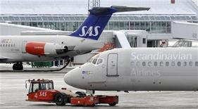A tow tractors moves a SAS MD-82 aircraft from Terminal 5 to Terminal 4 at Arlanda airport north of Stockholm, February 9, 2010. REUTERS/Johan Nilsson/Scanpix (SWEDEN - Tags: TRANSPORT BUSINESS)