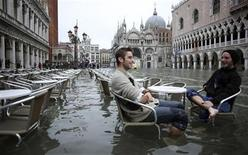 Tourists sit in St. Mark Square during a period of seasonal high water in Venice October 27, 2012. The water level in the canal city rose to 127 cm (50 inches) above the normal level, according to the monitoring institute. REUTERS/Manuel Silvestri