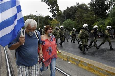 A couple hold a Greek flag as they walk past riot policemen during a violent protest against the visit of Germany's Chancellor Angela Merkel in Athens October October 9, 2012. REUTERS/John Kolesidis (GREECE - Tags: CIVIL UNREST POLITICS BUSINESS)