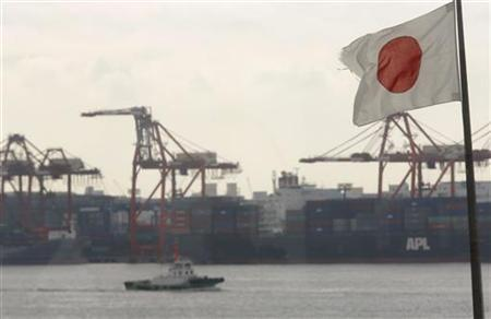 A Japanese flag flutters in front of a shipping container area, at a port in Tokyo November 12, 2012. REUTERS/Yuriko Nakao (JAPAN - Tags: BUSINESS EMPLOYMENT POLITICS)