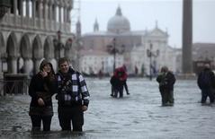 Casi tres cuartas partes de Venecia estaban inundadas y los turistas se veían obligados a bregar con el agua en la plaza de San Pedro el lunes, cuando el mal tiempo se extendía por el norte y el centro de Italia, obligando a la evacuación de 200 personas de sus casas en la Toscana. En la imagen, de 11 de noviembre, varias personas caminan en una calla inundada en Venecia. REUTERS/Manuel Silvestri