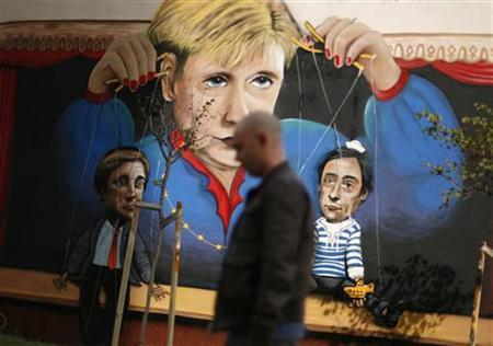 A man walks past a graffiti depicting German Chancellor Angela Merkel handling Portuguese Prime Minister Passos Coelho and Portugal's Foreign Minister Paulo Portas as if they were string puppets, in Lisbon October 23, 2012. REUTERS/Rafael Marchante (PORTUGAL - Tags: POLITICS BUSINESS)