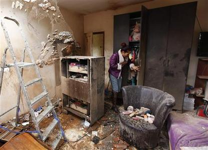 Tami Shadadi surveys the damage to her house in the southern town of Sderot November 12, 2012, after it was hit by a rocket fired by Palestinian militants in Gaza on Sunday. REUTERS/Amir Cohen