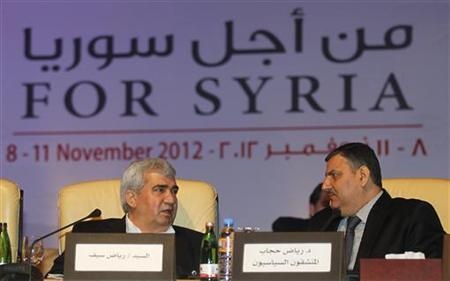 Leading Syrian dissident Riad Seif (L) speaks with former Syrian Prime Minister Riyad Hijab, who defected from the Assad regime, during the General Assembly of the Syrian National Council in Doha November 11, 2012. REUTERS/Mohammed Dabbous (QATAR - Tags: POLITICS CIVIL UNREST)