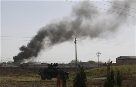 Smoke rises after an air strike on the Syrian town of Ras al-Ain, as a Turkish military vehicle is seen in the foreground from the Turkish border town of Ceylanpinar, Sanliurfa province November 12, 2012. REUTERS/Murad Sezer