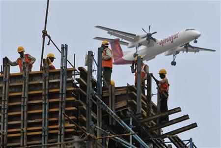 Construction workers erect scaffolding at the site of metro station as a SpiceJet Airlines aircraft flies past in the southern Indian city of Chennai May 14, 2012. REUTERS/Babu/Files