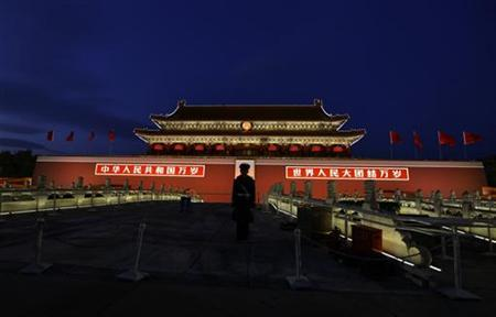 A paramilitary police officer stands guard in front of a giant portrait of the late chairman Mao Zedong at Beijing's Tiananmen Gate, November 12, 2012. REUTERS/Jason Lee
