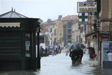Pessoas caminham por rua alagada de Veneza. Cerca de três quartos da cidade ficaram alagados nesta segunda-feira, e os turistas aproveitaram para nadar na Praça de São Marco, depois de fortes chuvas que atingiram a região norte e central da Itália, forçando 200 pessoas a deixarem suas casas na Toscana. REUTERS/Manuel Silvestri