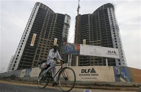 A man cycles past the construction site of a residential apartment building by DLF Ltd. in Gurgaon January 27, 2010. REUTERS/Adnan Abidi/Files