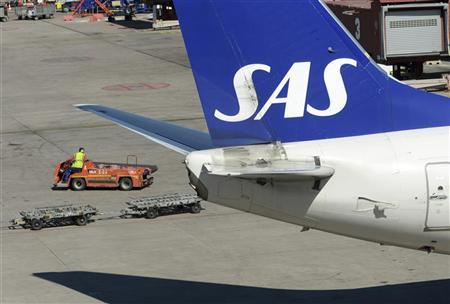A baggage belt truck passes behind the tail of a Scandinavian airline SAS Boeing 737 aircraft at the Stockholm-Arlanda airport in Sweden May 3, 2012. SREUTERS/Johan Nilsson/Scanpix