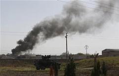 <p>Una columna de humo emerge desde el poblado sirio de Ras al-Ain tras un ataque aéreo, mientras un vehículo militar turco se aprecia en el fondo de la imagen en el poblado fronterizo de Ceylanpinar, nov 12 2012. Aviones de combate sirios atacaron el lunes una zona junto a la frontera con Turquía y bombardearon la localidad de Ras al-Ain que está controlada por rebeldes, mientras Ankara se mostraba cada vez más preocupada por su seguridad y la OTAN dijo que tomaría las medidas necesarias para defender a su estado aliado. REUTERS/Murad Sezer</p>