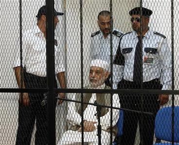 Baghdadi al-Mahmoudi, who was the last prime minister of Libya's Gaddafi government, sits behind bars during the first hearing of his trial at a prison facility in Tripoli November 12, 2012. REUTERS/Ismail Zitouny