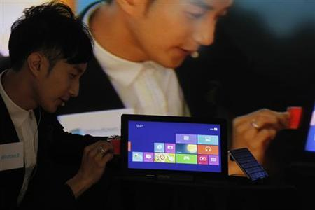 A magician performs with a tablet loaded with Microsoft's new Windows 8 during the launch of this new operating system in Hong Kong October 26, 2012. REUTERS/Bobby Yip/Files