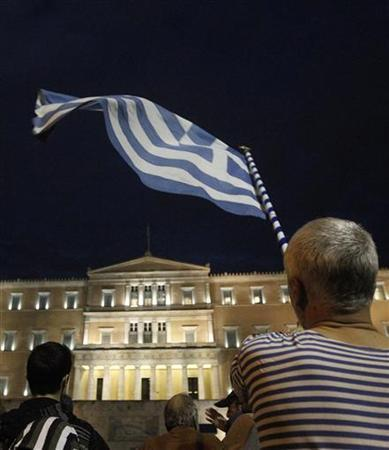 A protestor waves Greek flag in front of the parliament in Syntagma square during a 48-hour strike by the two major Greek workers unions in central Athens November 7, 2012. Greek police fired teargas to disperse protesters throwing petrol bombs and stones outside parliament, where lawmakers were due to vote on a package of deeply unpopular austerity cuts on Wednesday. REUTERS/John Kolesidis (GREECE - Tags: CIVIL UNREST POLITICS BUSINESS EMPLOYMENT)